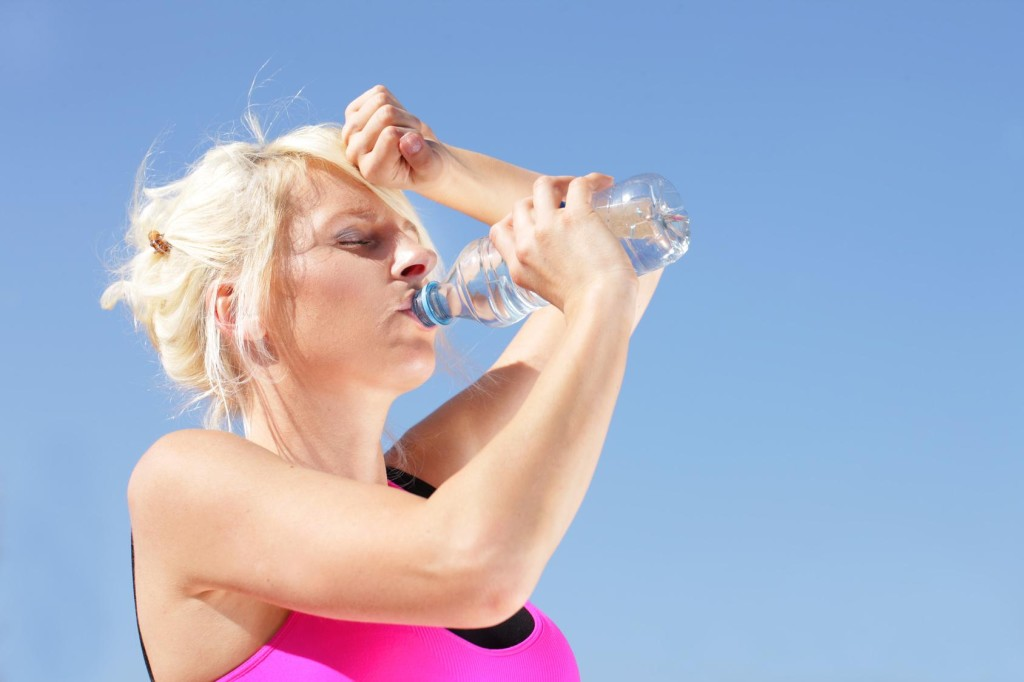 Woman with water bottle feels the heat of summer